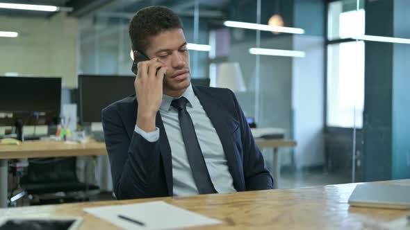 Thumbnail for Young African Businessman Talking on Smartphone in Office