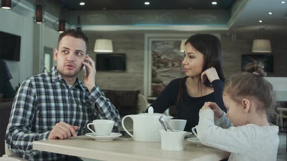 Thumbnail for Mother Trying To Attract Father's Attention To Daughter While He Is Busy Talking To Phone