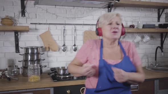 Thumbnail for Funny Caucasian Old Woman in Headphones Singing and Dancing at the Kitchen, Mature Cheerful Retiree