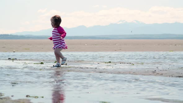 Thumbnail for Little Girl Walking On Pacific Northwest Sandy Ocean Beach