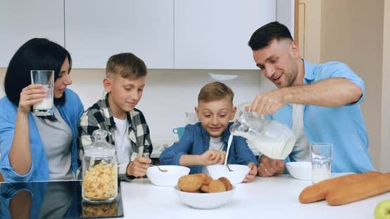 Thumbnail for Dad Filling Milk Into Bowl with Corn Flakes His Two Sons During Family Breakfast