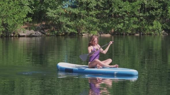 Young Fitness Woman Paddling Along Lake