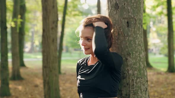 Fröhliche Frau entspannt sich im Park während des Trainings