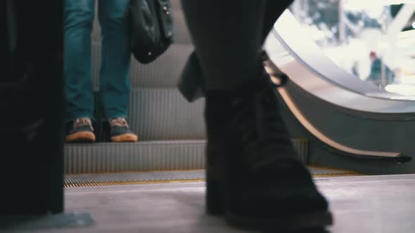 Thumbnail for People's Feet Go Down the Escalator Lift in the Mall. Shopper's Feet on Escalator in Shopping Center