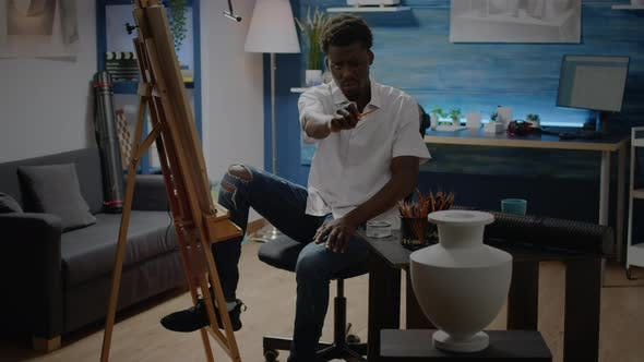 African American Man Studying Vase Design with Pencil
