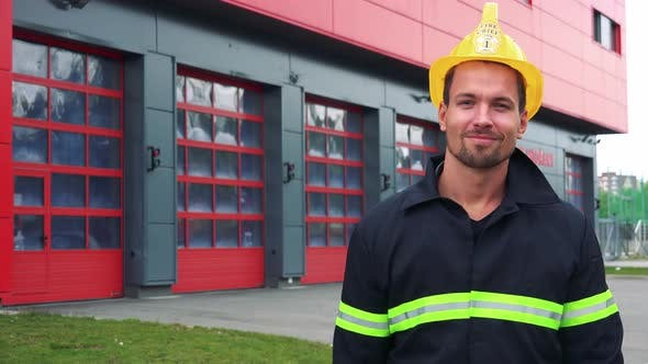 Thumbnail for A Young Firefighter Puts on a Helmet and Smiles at the Camera with Hands Folded Across His Chest