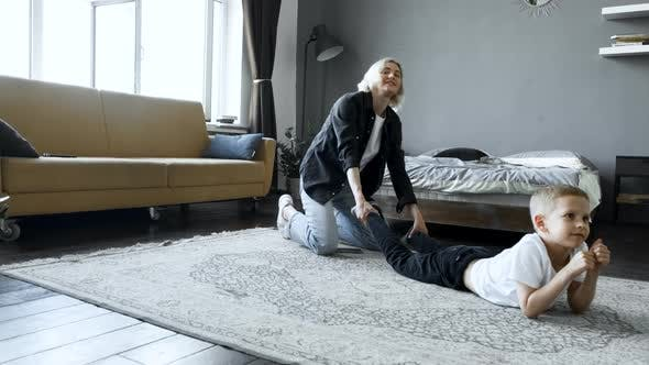 Young Blonde Woman Mother Plays With A Small Child Son In The Room, Lying on The Floor