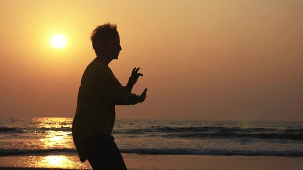 Silhouette of Active Senior Woman Practicing Tai Chi Gymnastic on Sandy Beach.
