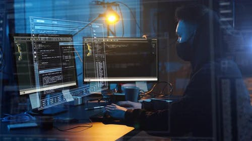 Hacker in Mask with Computer Making Cyber Attack