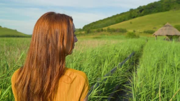 Woman with ginger hair walking outdoors