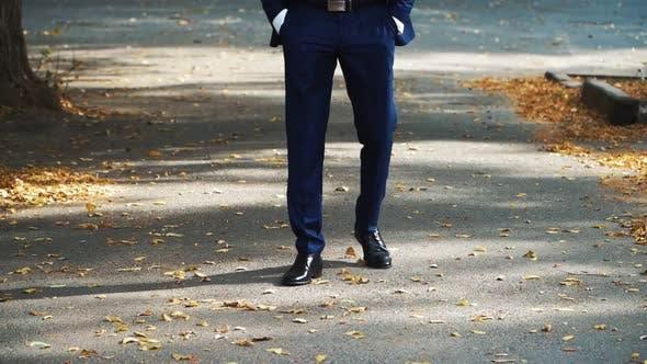 Ein Geschäftsmann in schwarzen Schuhen geht in einem Herbstpark auf einer Asphaltstraße