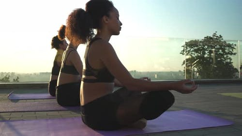 Fit Sporty Active Ethnic Women Group Meditating at Outdoor Group Yoga Class