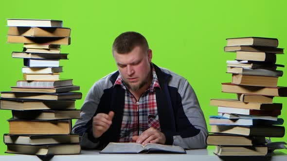 Thumbnail for Man Leafing Through a Textbook, It Suffers From Headaches. Green Screen