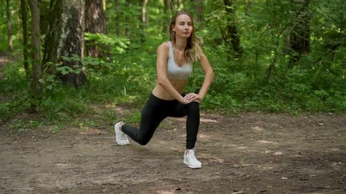 Young Woman Warms Up Before a Fitness Workout in the Park. A Healthy Young Woman Is Warming Up in