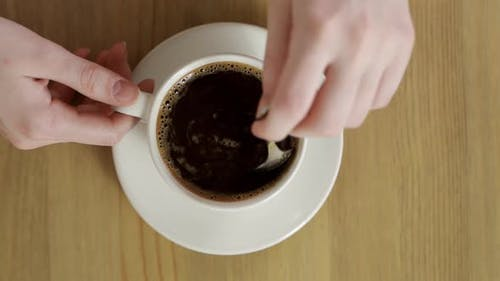 Delicious and Flavored Hot Coffee Rotating in White Cup After It Was Stirred