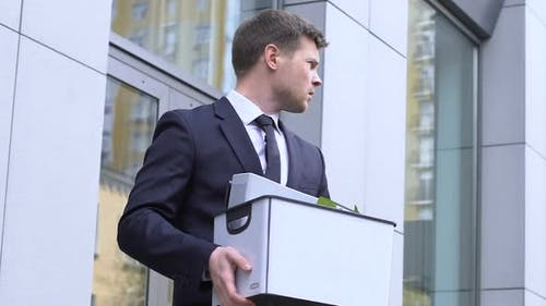 Young Man Carrying Box With Personal Belongings, Depressed About Dismissal