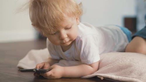 Little Blond Toddler Lies on Floor