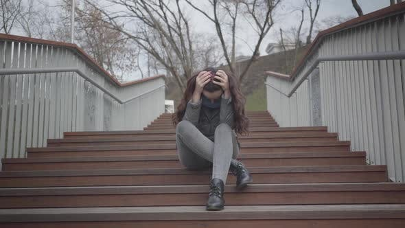 Thumbnail for Portrait of Depressed Caucasian Girl Sitting on Stairs in City Park and Crying. Beautiful Brunette
