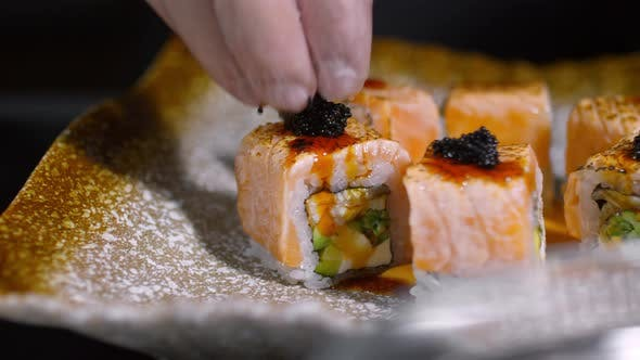 Thumbnail for Cook Putting Black Caviar on Sushi Rolls