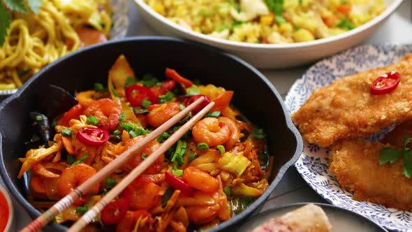 Asian Food Served. Plates, Pans and Bowls Full of Noodles Chicken Stir Fry and Vegetables