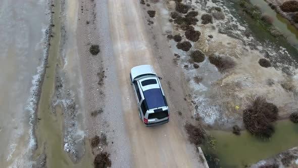 Car Going on Dirt Road on Arid Barren Desert