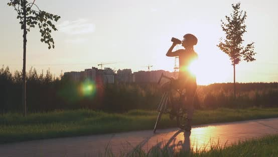 Thumbnail for Woman cyclist is drinking water after bike ride in park against sunset. Triathlon concept