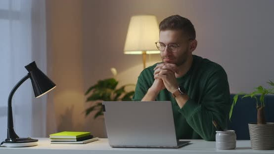 Thumbnail for Man with Glasses Is Sitting in Front of Laptop Thinking and Typing on Keyboard Working at Evening at