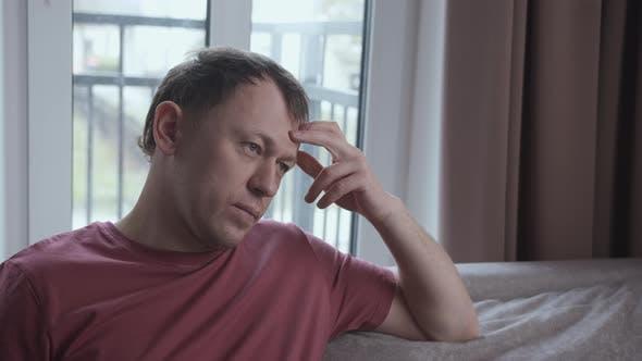Portrait of Serious Man on Sofa Negative Emotions Window Background