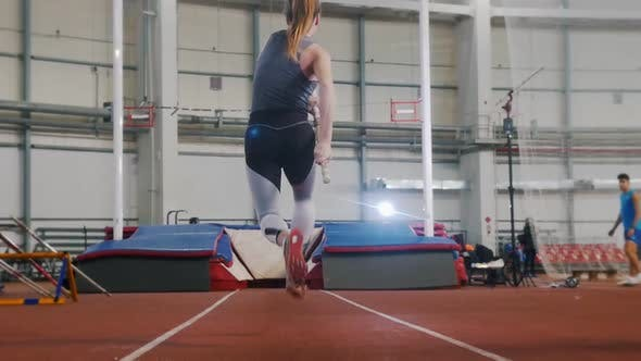 Thumbnail for Pole Vaulting Indoors - a Young Woman with Ponytail Running Up and Jumping Over the Bar
