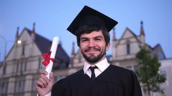 Thumbnail for Caucasian Happy Young Graduated Man Posing To the Camera and Showing His Diploma in Front of the