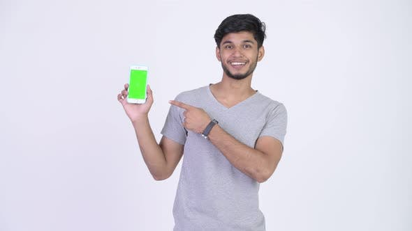 Cover Image for Young Happy Bearded Indian Man Showing Phone and Giving Thumbs Up
