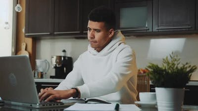 Black Man in White Hoodie Working Home on the Computer