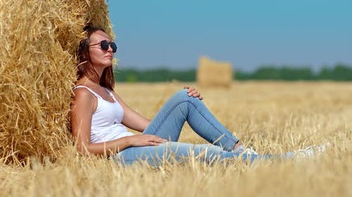 Portrait a Girl in Sunglasses Resting By a Golden Haystack Resting in Nature