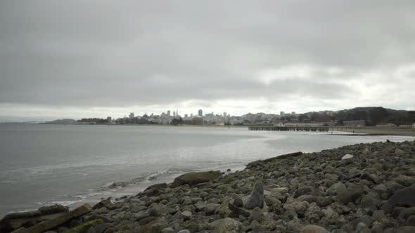 Thumbnail for San Francisco cityscape under grey sky as seen from coastline