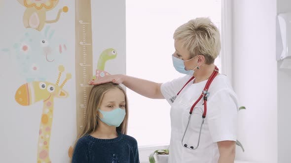 Friendly Paediatrician Measuring Little Girl's Height at a Consult