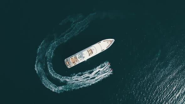 Aerial view of two Jet Ski ride around Super Yacht at Sunset.