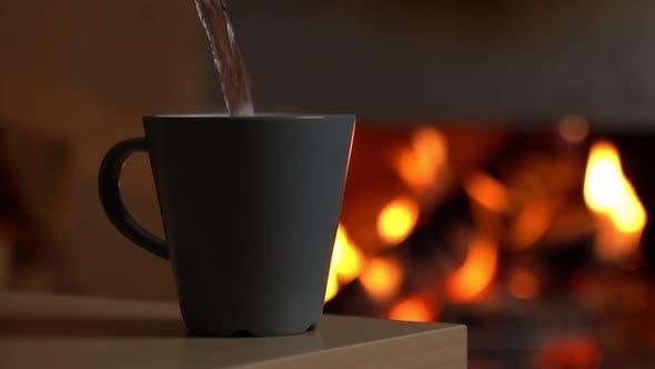 Heißes Wasser wird vor dem Hintergrund des Kamins in eine Tasse gegossen