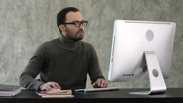 Thumbnail for Man Working On Computer In IT Office, Sitting At Desk Writing Codes