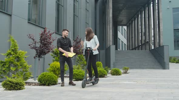 A Man Is Waiting for a Woman Who Arrives on an Electric Scooter. Men and Women Businessmen Meeting