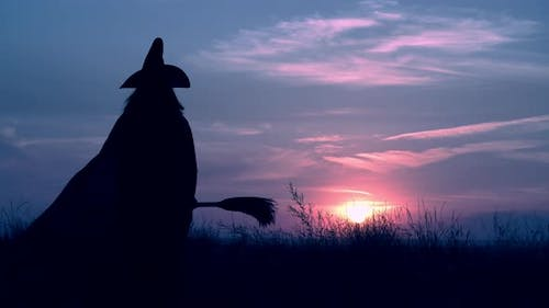 a Witch with Besom Posing on the Hill Halloween Evening Skyline