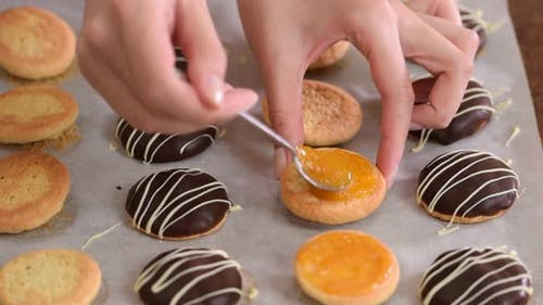 Close-up of a Woman Hand Applying Apricot Jam on Cookies.
