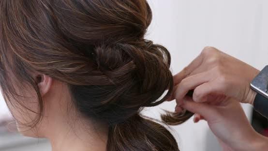 Hairdresser creat hairstyle for bride in salon