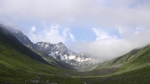 High Snowy Mountains on the Background of Glacial Valley and Alpine Meadows