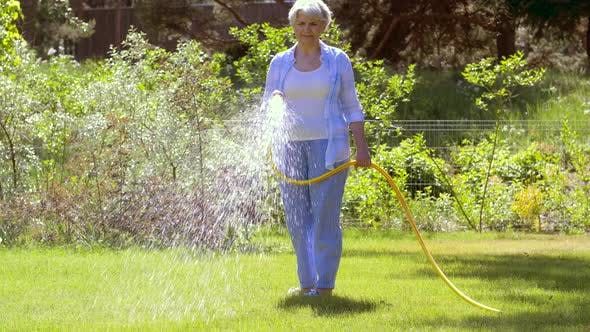Thumbnail for Senior Woman Watering Lawn By Hose at Garden 35