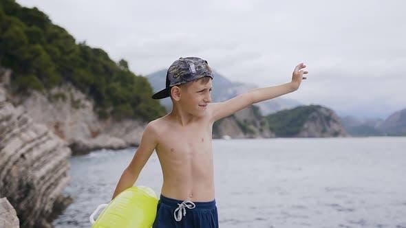 Thumbnail for Little Boy Stand auf dem Felsen und Blick über das Meer bei der Sonnenuntergang
