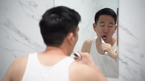 Asian Man Cleaning Teeth Using Electric Toothbrush