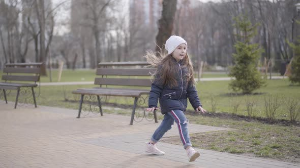 Wide Shot of Joyful Kid Having Fun in Park on Sunny Day. Cheerful Caucasian Little Girl Running and