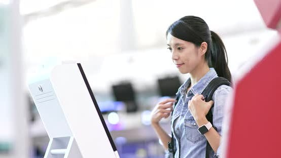 Thumbnail for Asian Woman using selfie check in machine in the airport