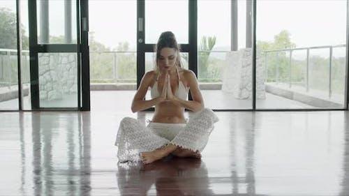 barfuß frau meditieren in geräumigem zimmer