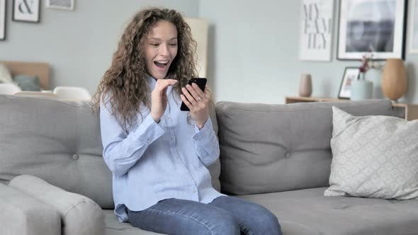 Cover Image for Curly Hair Woman Cheering Success on Smartphone while Sitting on Couch